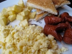 Scrambled eggs with sausage, toast and potatoes